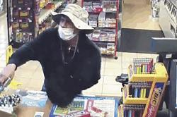 This March 26, 2020 image from surveillance video shows a man, believed to be William Rosario Lopez wearing a surgical mask, with a gun in a Connecticut convenience store.