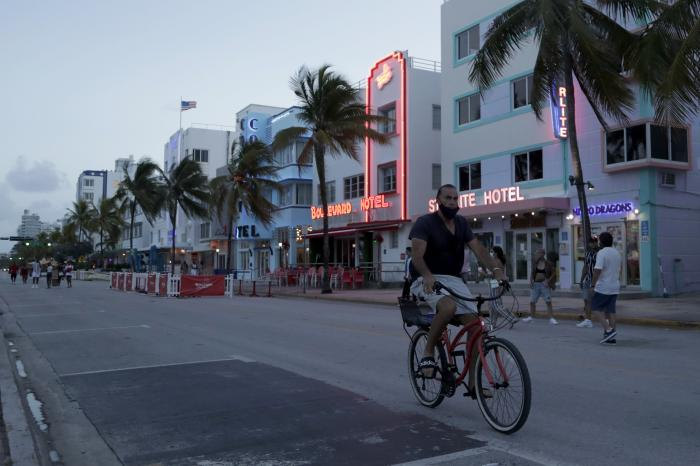 In this July 24, 2020, file photo, a sparse crowd is on Ocean Drive after an 8 p.m. curfew amid the coronavirus pandemic in Miami Beach, Fla.