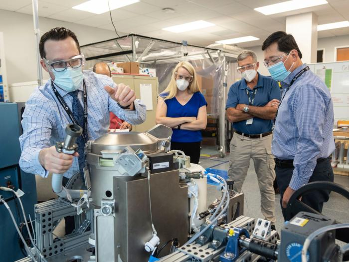 In this June 18, 2020 photo provided by NASA, astronaut Kate Rubins, center, and support personnel review the Universal Waste Management System, a low-gravity space toilet, in Houston