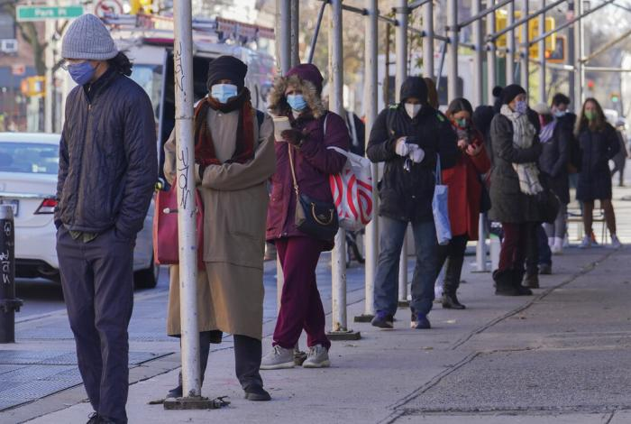 People wait on a line stretching around a block for a clinic offering COVID-19 testing in Brooklyn, New York.