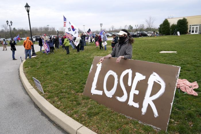 Supporters of President Donald Trump, left, gather as a counter protester holds a sign outside of the Wyndham Hotel where the Pennsylvania State Senate Majority Policy Committee is scheduled to meet, Wednesday, Nov. 25, 2020, in Gettysburg, Pa. (AP Photo/Julio Cortez)