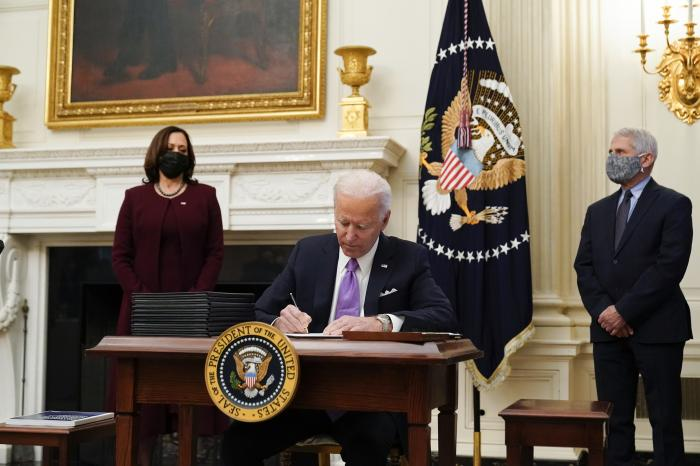 President Joe Biden signs executive orders after speaking about the coronavirus, accompanied by Vice President Kamala Harris, left, and Dr. Anthony Fauci, director of the National Institute of Allergy and Infectious Diseases, right, in the State Dinning Room of the White House.