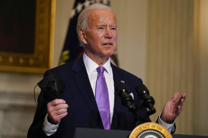 President Joe Biden holds his face mask as he delivers remarks on COVID-19, in the State Dining Room of the White House, Tuesday, Jan. 26, 2021, in Washington.