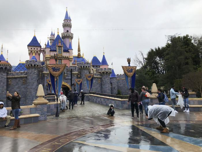 Visitors take photos at Disneyland in Anaheim, Calif.