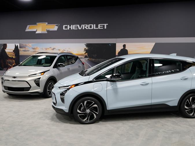 The 2022 Bolt EV, foreground, and EUV are displayed, Thursday, Feb. 11, 2021, in Milford, Mich.