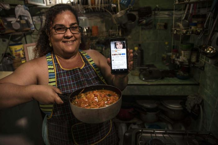 "Contributor Yuliet Colon poses for a photo holding a pot of her creation, ""Cuban-style pisto manchego,"" and her phone that displays the Facebook page, ""Recipes from the Heart."""