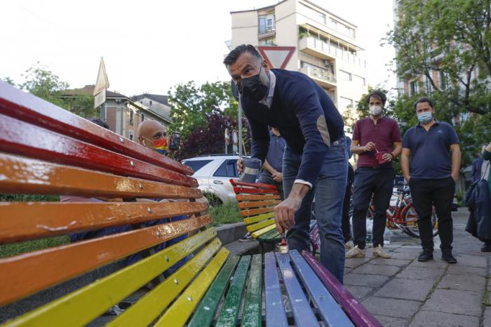 In this Friday, May 7, 2021 filer, Italian lawmaker Alessandro Zan paints a bench in the colors of the rainbow, in Milan, Italy.