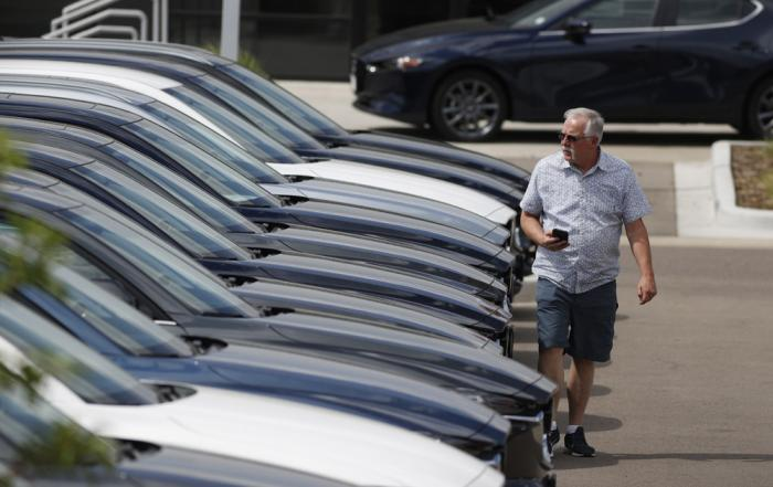 In this Sunday, June 14, 2020, photograph, a prospective buyer looks over a long row of unsold 2020 CX-5 sports-utility vehicles sedans sits at a Mazda dealership in Littleton, Colo.